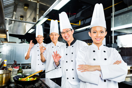 Asian Indonesian chefs along with other cooks in restaurant or hotel kitchen cooking or fry with a pan at the stove photo