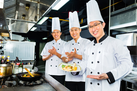 Asian Indonesian chefs along with other cooks in restaurant or hotel kitchen cooking or fry with a pan at the stove Imagens - 33784814