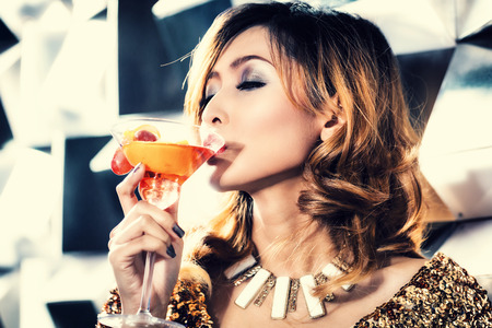 indonesian woman: Asian girl drinking cocktail in fancy nightclub or bar
