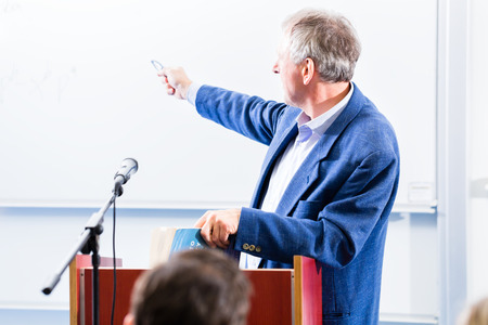 professor: College professor giving lecture for students standing at desk Stock Photo