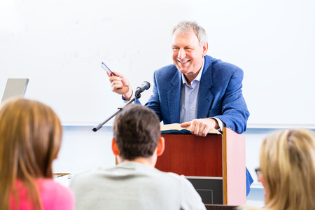 lecture room: College professor giving lecture for students standing at desk Stock Photo