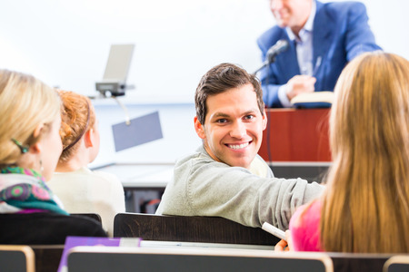 discourse: College professor giving lecture for students standing at desk Stock Photo