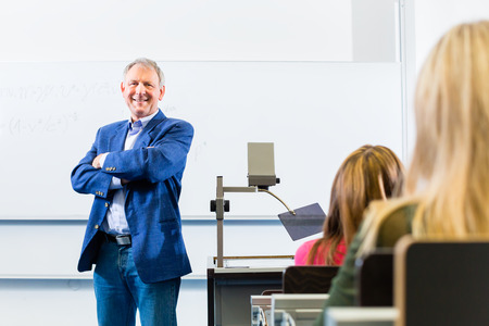 discourse: College professor giving lecture in college standing at desk Stock Photo
