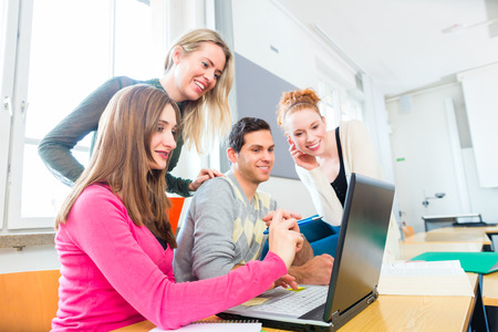 computer lesson: University college students using laptop for project team work learning Stock Photo