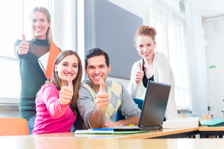 computer lesson: University college students using laptop for project team work giving the thumbs up sign Stock Photo