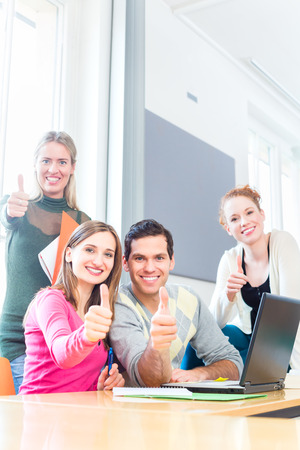thumbs up sign: University college students using laptop for project team work giving the thumbs up sign Stock Photo