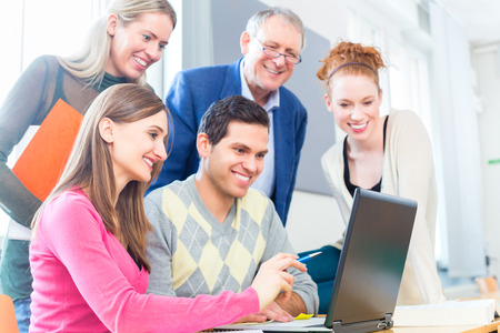 college professor: University college students with professor in seminar using laptop for project team work Stock Photo