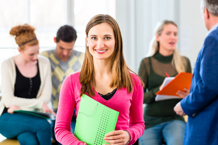University college student standing in class room with professor photo