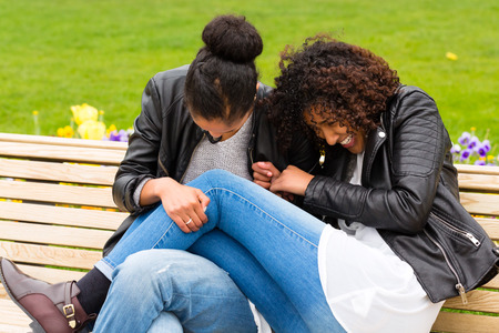 bff: Two north African teen friends sitting together on park bench talking