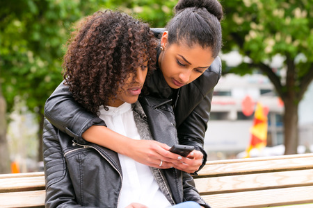 bff: Two north African teen friends reading and writing text message on mobile phone in park
