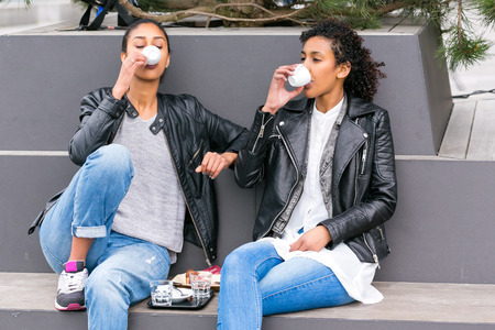 bff: Two north African teen friends drinking together coffee outside Stock Photo