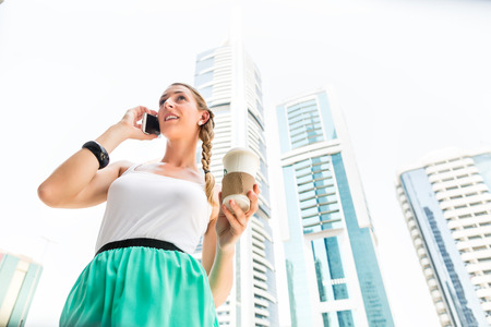 telephoning: Young woman telephoning with mobile phone, drinking coffee in metropolitan city Dubai
