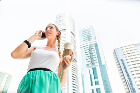 metropolitan: Young woman telephoning with mobile phone, drinking coffee in metropolitan city Dubai