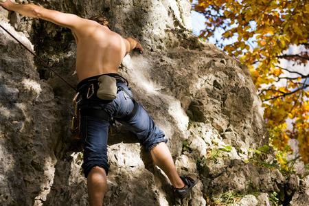 rock climbing man: Man climbing a rock short before reaching the summit Stock Photo