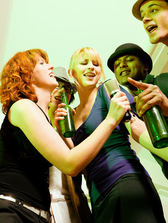 Group of friends (diversity) at a party in a club doing karaoke and drinking beer photo