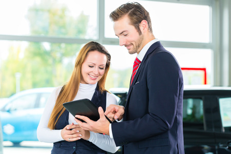 Seller or car salesman and female client or customer in car dealership presenting the interior decoration of new and used cars in the showroom on tablet computer Stockfoto