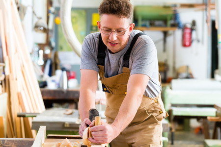 wood planer: Carpenter working with a wood planer on workpiece in his workshop or carpentry