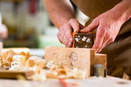 Timmerman werken met een schuurblok en schuurpapier in zijn atelier
