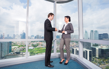 deal in: business people handshake to seal deal in front of city skyline