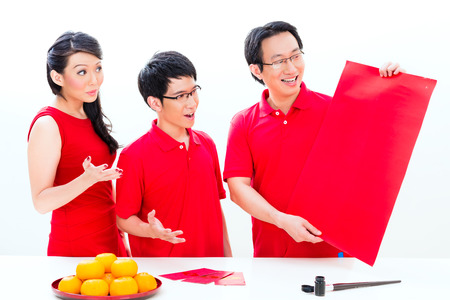 Friends family celebrate Chinese new year with traditional calligraphy, wearing red shirts photo