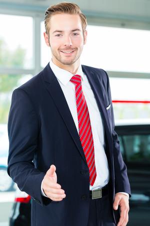 提示ショールームで彼の新しいと中古車中古車販売店の売り手または車のセールスマン