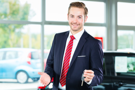 auto dealership: Seller or car salesman in car dealership with key presenting his new and used cars in the showroom