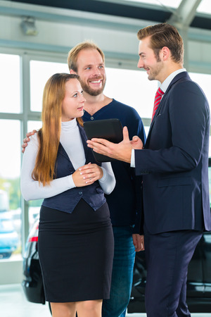Seller or car salesman and clients or customers in car dealership presenting the interior decoration of new and used cars in the showroom on tablet computer photo