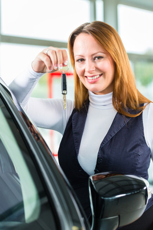 test drive: Young woman beside a new car in car dealership, obviously she is buying the auto, or making a test drive and holding the keys in hand