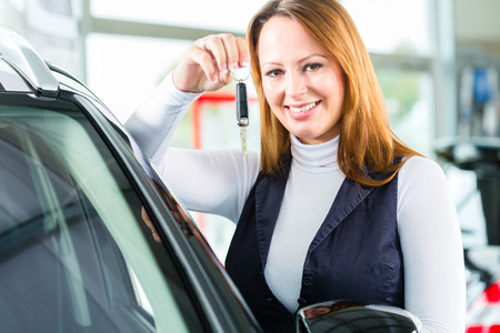 car dealership: Young woman beside a new car in car dealership, obviously she is buying the auto, or making a test drive and holding the keys in hand