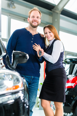 bought: Young couple or customers in car dealership they bought a auto or new car