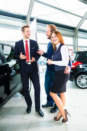 car showroom: Seller or car salesman and clients or customers in car dealership presenting the interior decoration of new and used cars in the showroom Stock Photo
