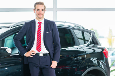car dealer: Seller or car salesman in car dealership presenting his new and used cars in the showroom Stock Photo