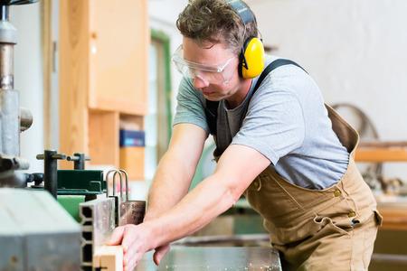 Carpenter werken aan een elektrische cirkelzaag te snijden boards, is hij het dragen van een veiligheidsbril en gehoorbescherming voor veiligheid op de werkplek