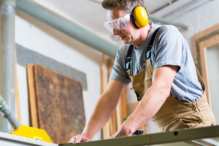 hearing protection: Carpenter working on an electric buzz saw cutting some boards, he is wearing safety glasses and hearing protection for workplace safety