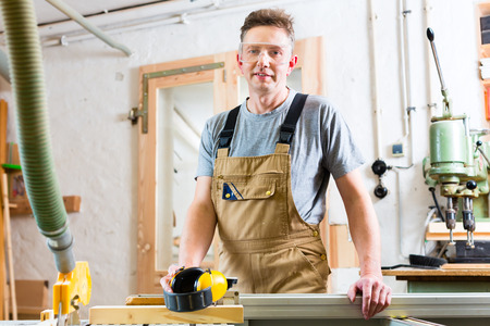 Carpenter working on an electric buzz saw cutting some boards photo