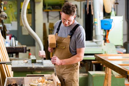 Schreiner mit Beitel und Hammer in seiner Werkstatt