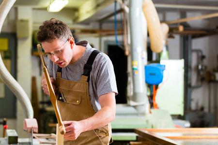 serrucho: Carpintero que trabaja en una sierra manual cortar una espiga en los cajones en su taller con arco o bastidor de la sierra