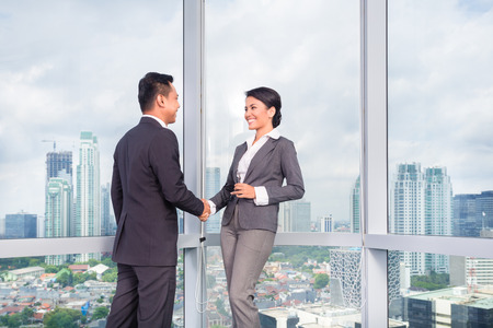 business people handshake to seal deal in front of city skyline photo