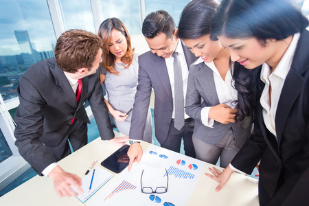 Mixed business team discussing earnings with financial graphs on the table Stock Photo