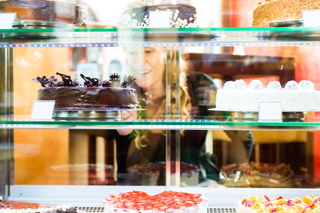 french bakery: Woman selecting a cake from the pastry shop glass display