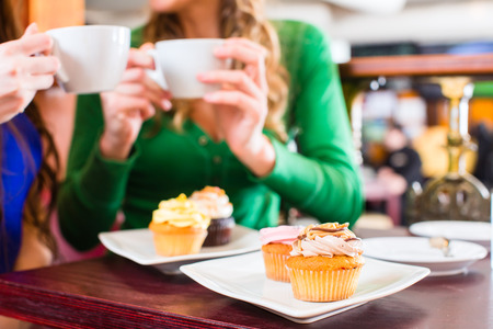 treat: Friends having fun and eating muffins at bakery or pastry shop Stock Photo