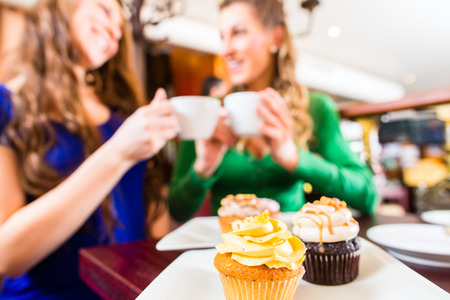 drinking tea: Friends having fun and eating muffins at bakery or pastry shop Stock Photo