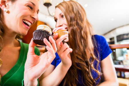 coffee and tea: Friends having fun and eating muffins at bakery or pastry shop Stock Photo
