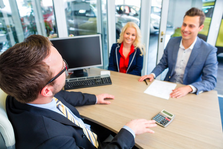 Leasing: Couple buying car at dealership and negotiating price with salesman Stock Photo