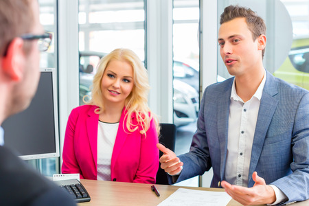 Couple buying car at dealership and negotiating price with salesman Archivio Fotografico