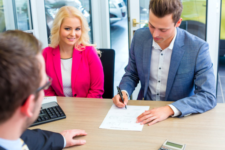 Couple buying car at dealership and signing sales contract with salesman photo