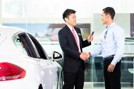 Aziatische Car Salesman verkoopt auto naar de klant Stockfoto