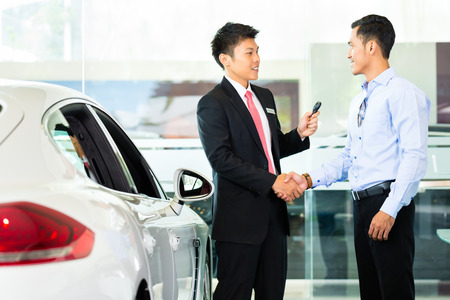 Asian Car Salesman selling auto to customer Stock Photo