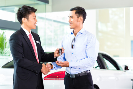 Asian Car Salesman selling auto to customer Imagens