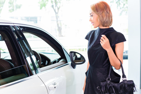 indonesian woman: Mujer indonesia asi�tica comprar coche SUV maravillado por la belleza del auto Foto de archivo